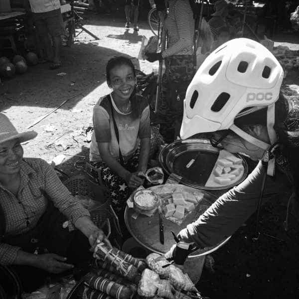 Cyclist in POC helmet shopping at a Cambodian market during a bicycle tour