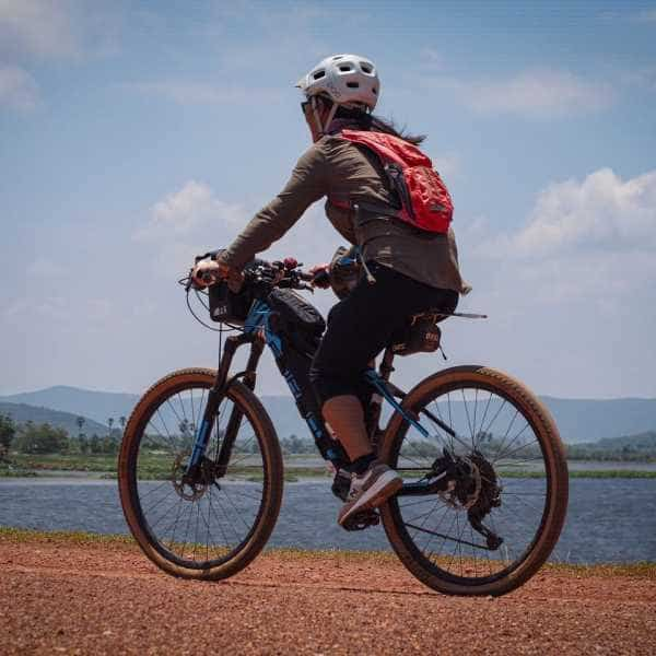 Gravel cyclist cycling past a lake in Cambodia
