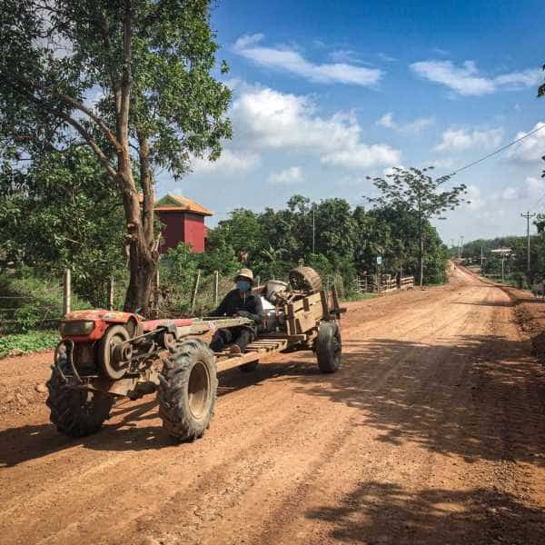 Cambodian tractor on red gravel road during cycling tour
