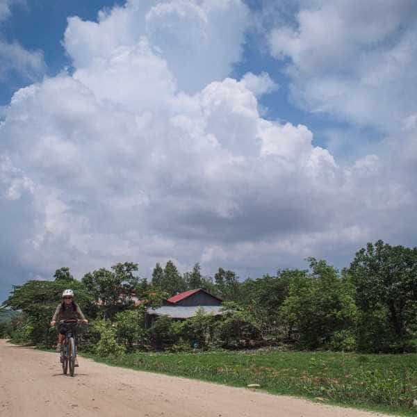 Gravel cyclist on white gravel road in Cambodia