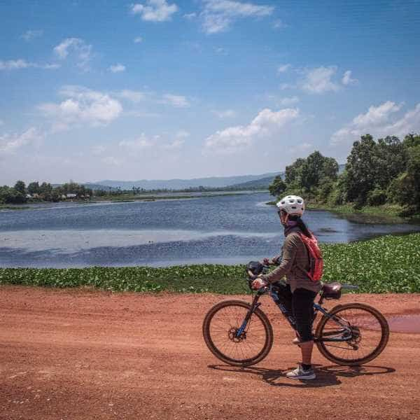 Gravel cyclist on red gravel road in Cambodia