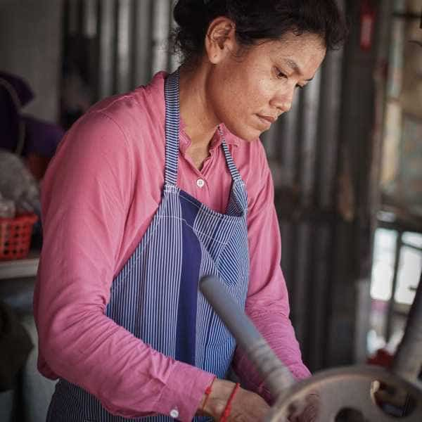 Khmer lady squeezing sugarcane juice during a cycling tour in Cambodia
