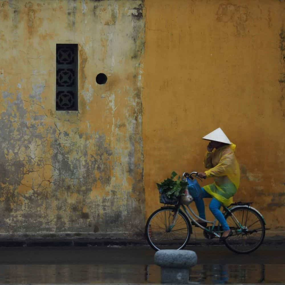 Lady cyclist in a conical hat passes a yellow wall