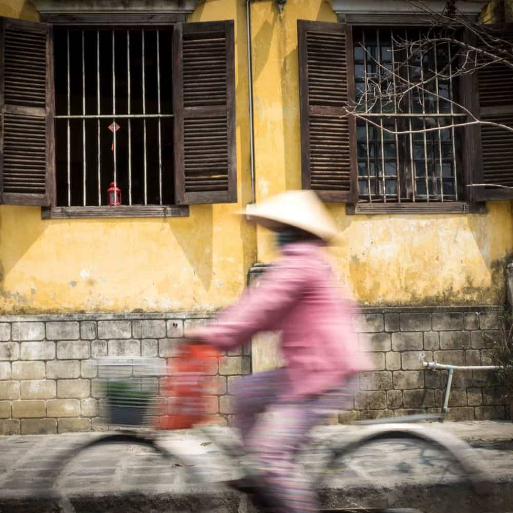 Cyclists and yellow wall in Hoi An
