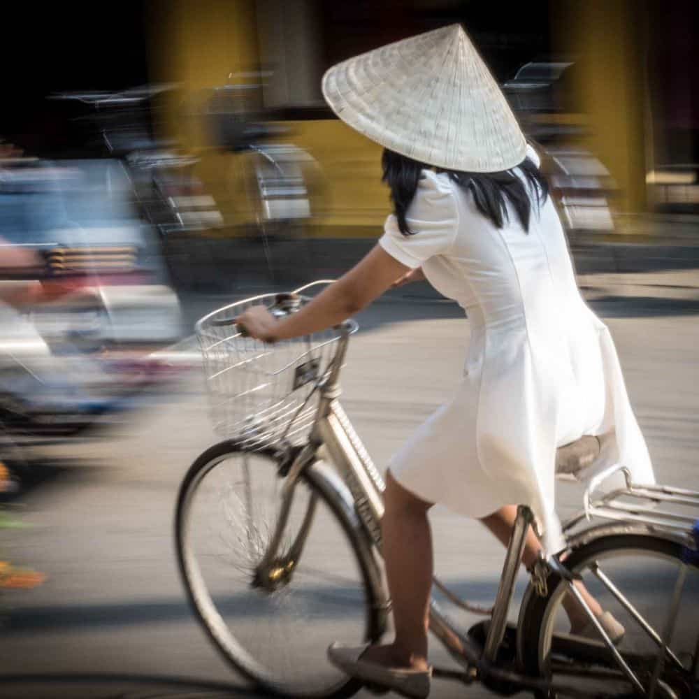 A Vietnamese girl in a white dress and conical hat on a bicycle