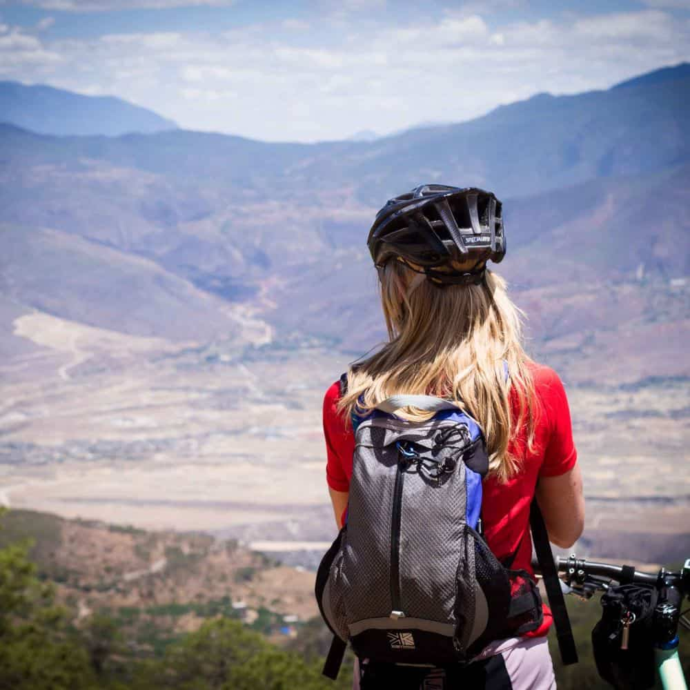 A girl take a break so admire the view during a cycling holiday in Yunnan, China