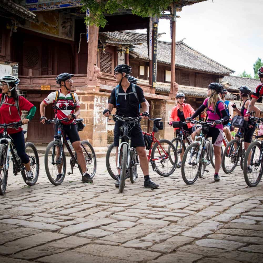 cyclists arrive in Shaxi during a tour of Yunnan in China