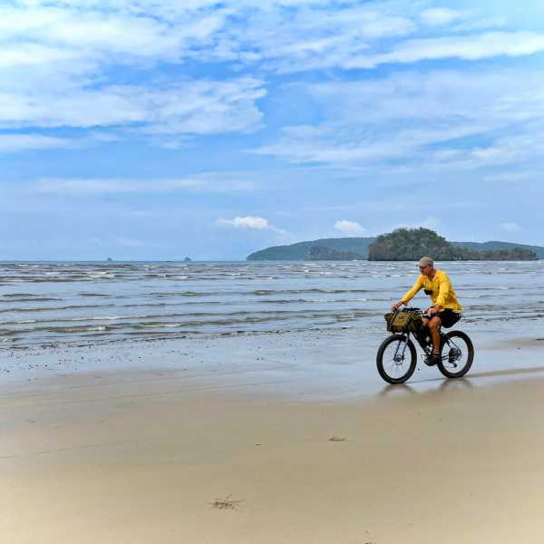 A cyclists riding on the beach whilst bike packing in Thailand