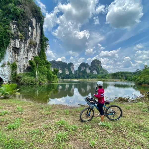 A lady cyclists looks across a lake a karst rocks whilst touring southern Thailand