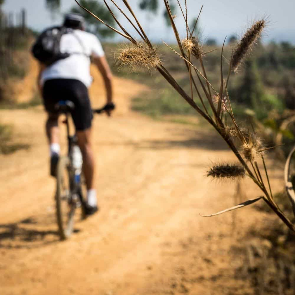 a cyclist on a gravel road in north thailand