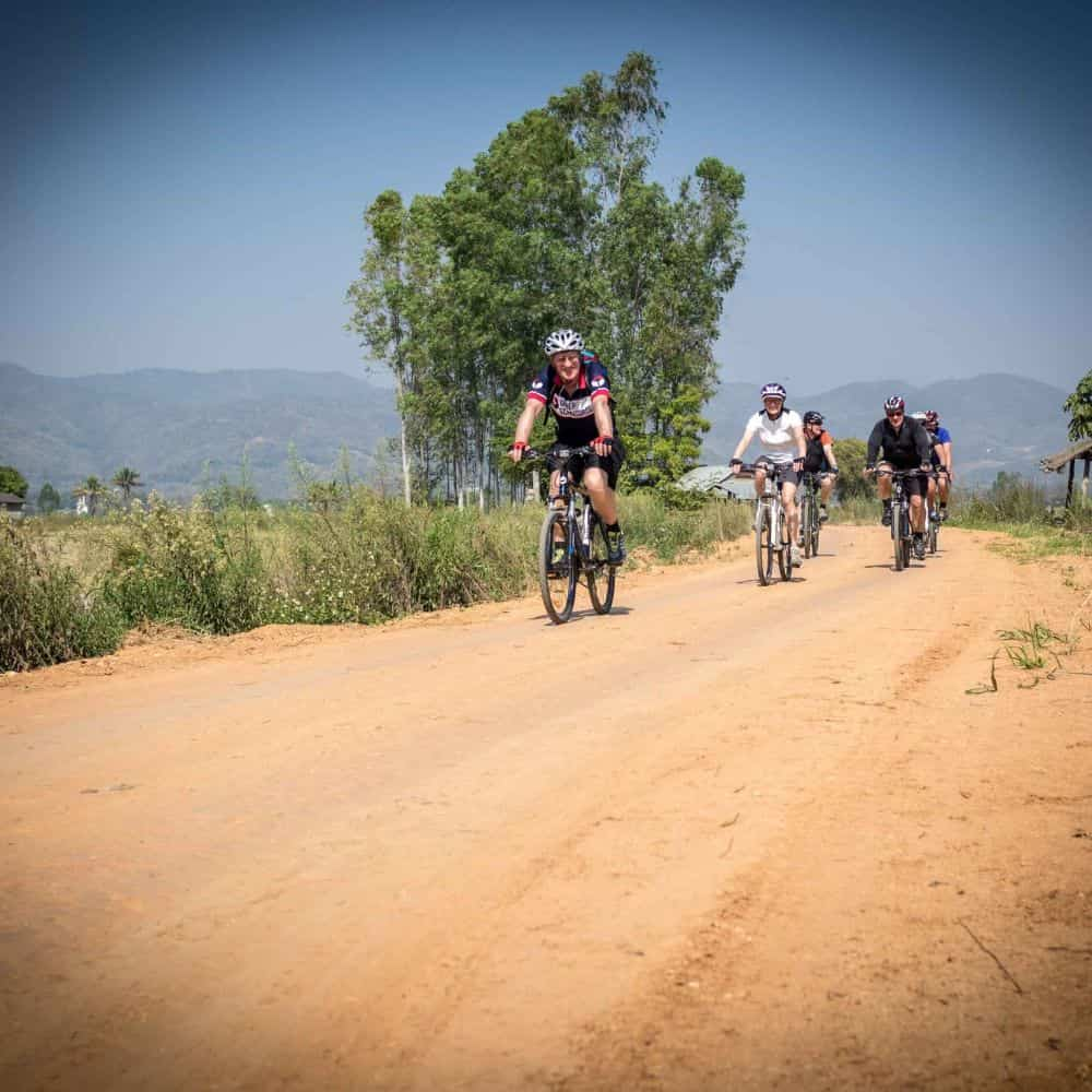 Cyclists on gravel road on tour in north Thailand