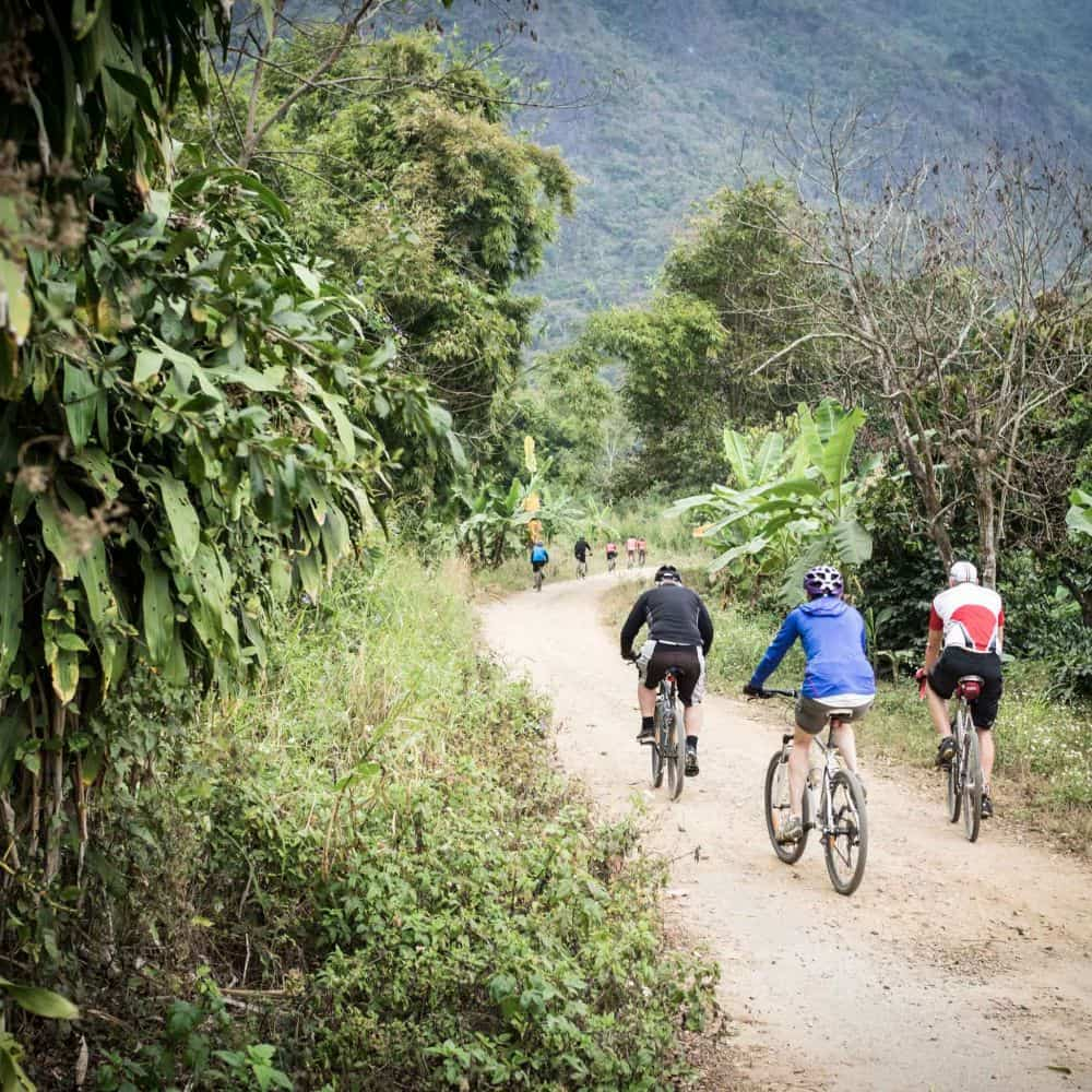 touring cyclists on a gravel road in north Thailand
