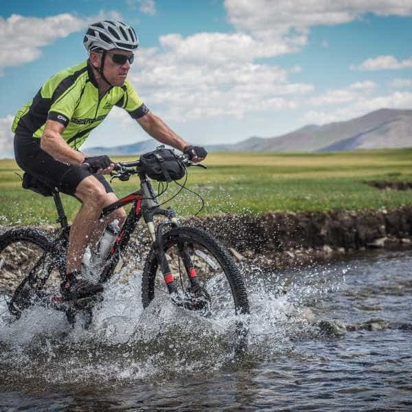 A cyclist crossing a river in Mongolia