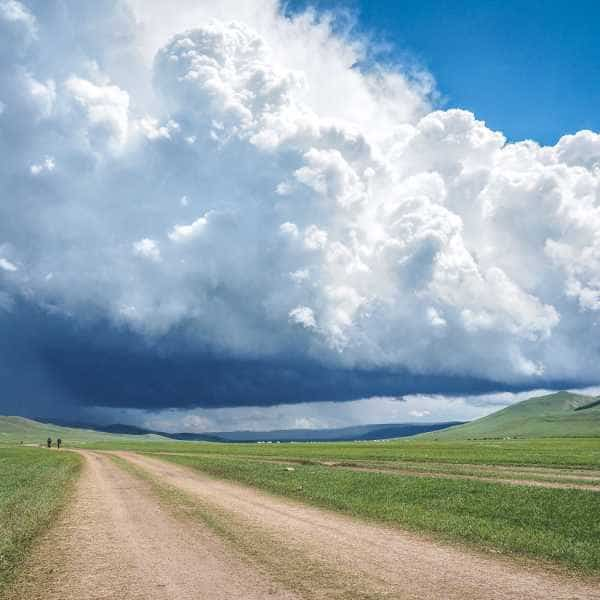 cyclist on a wide gravel road beneath a dramatic sky in Mongolia