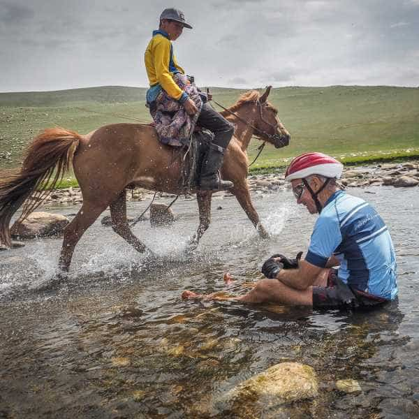 A cyclist in a river meets a mongolian  horse rider