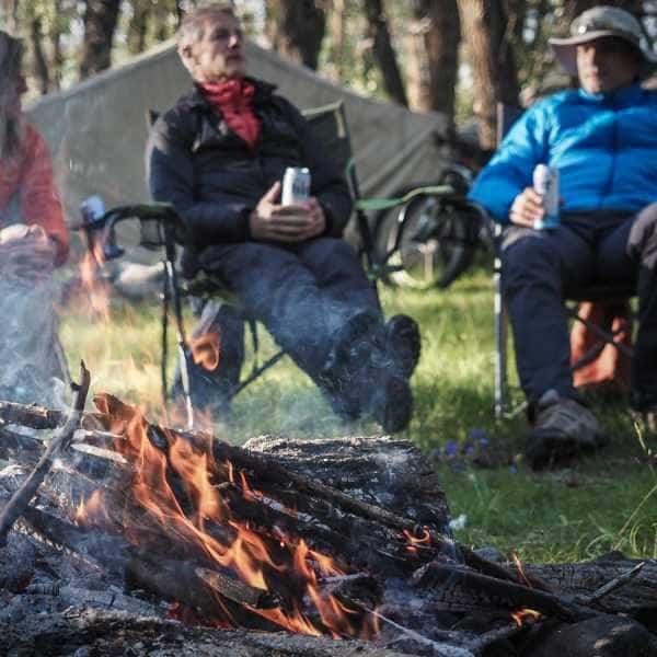 Cyclists by a camp fire whilst on tour in Mongolia