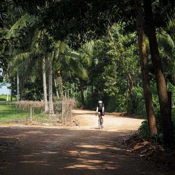 A cyclist on a gravel road in Thailand