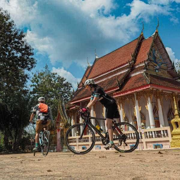 Cyclists passing a Thai Temple during a cycling holiday