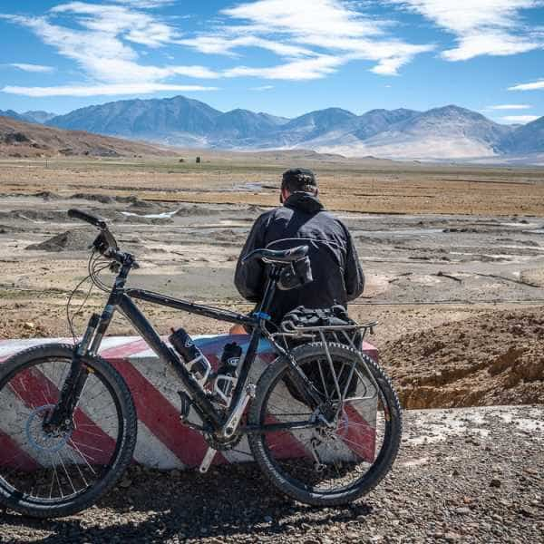 A lone cyclists takes a rest whilst cycling Lhasa to Kathmandu Tibet