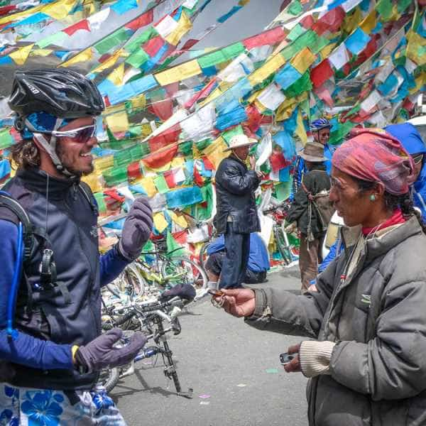 A cyclist meets a Tibetan lady beneath colourful prayer flags whilst cycling Lhasa to Kathmandu Tibet
