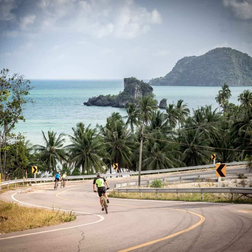 a group of cyclists on a winding coastal road in south Thailand