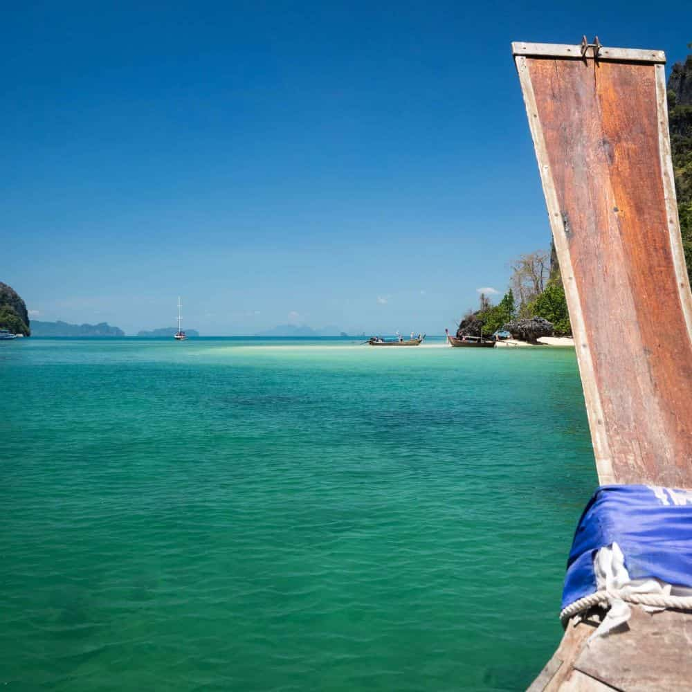 a long tail boat on an azure sea whilst ferrying touring cyclists in Thailand