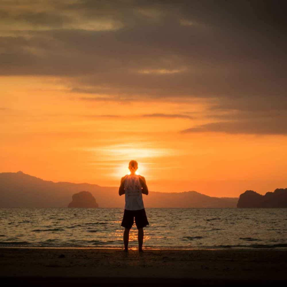 A man practising Yoga in front of a rising sun on a Thai beach