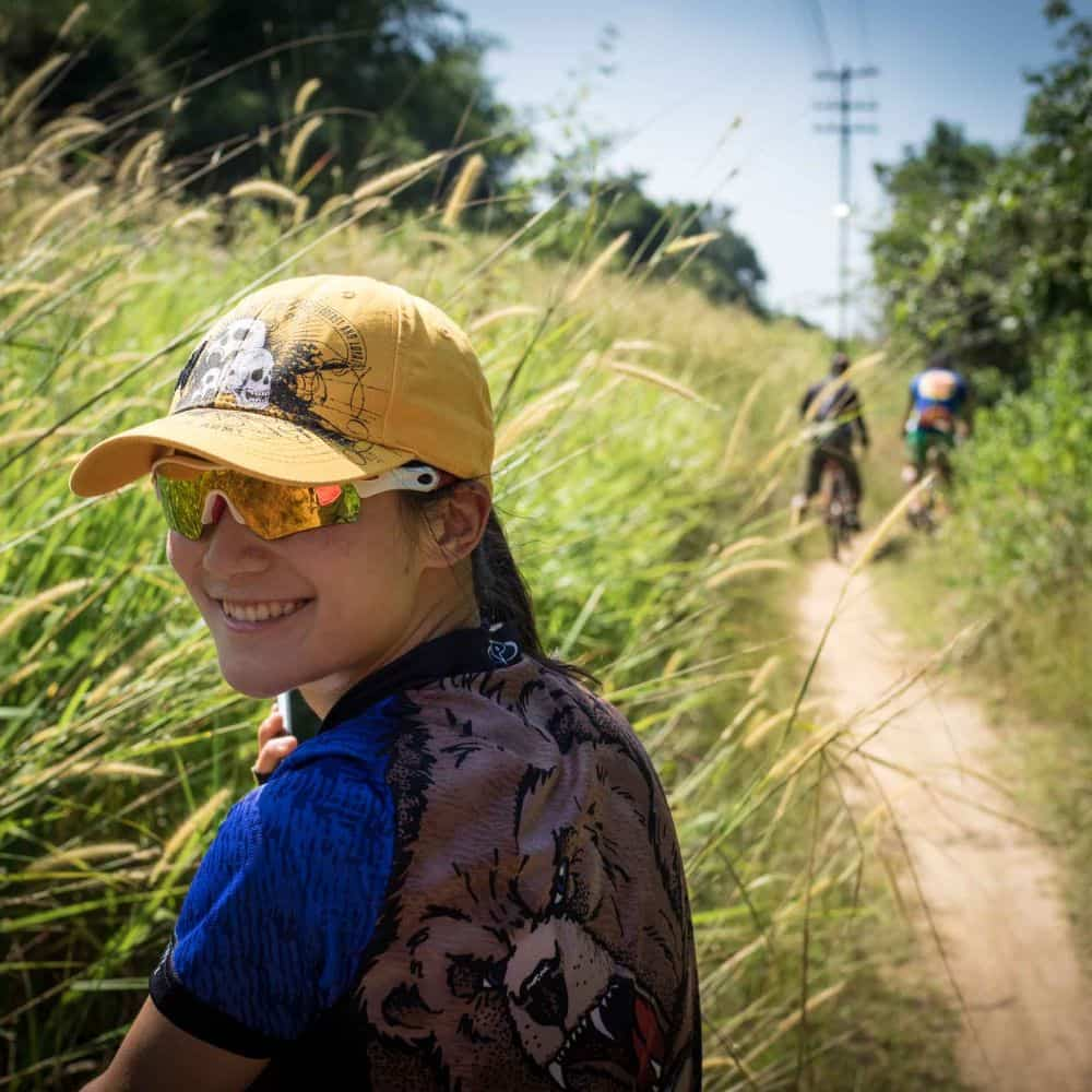 A young Chinese lady cyclists on a gravel track during a Thailand bicycle tour