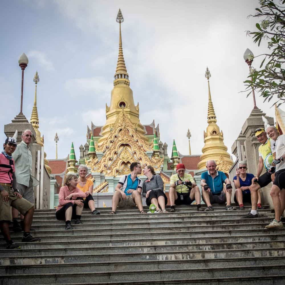 A group of touring cyclists relax outside a temple in southern Thailand