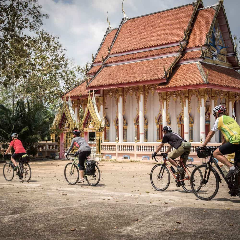 Cyclists on a touring holiday in Thailand passing aThai temple