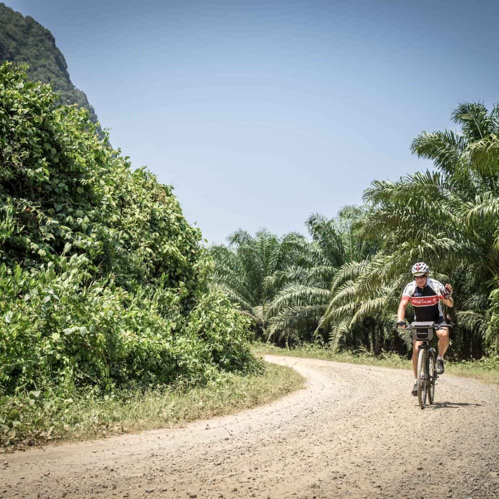 A touring cyclist on a gravel road during a south Thailand cycling holiday