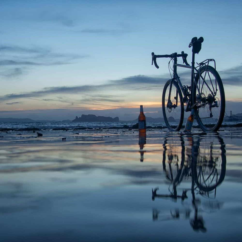 A gravel bicycle and a bottle of beer on a south Thailand beach as the sun sets