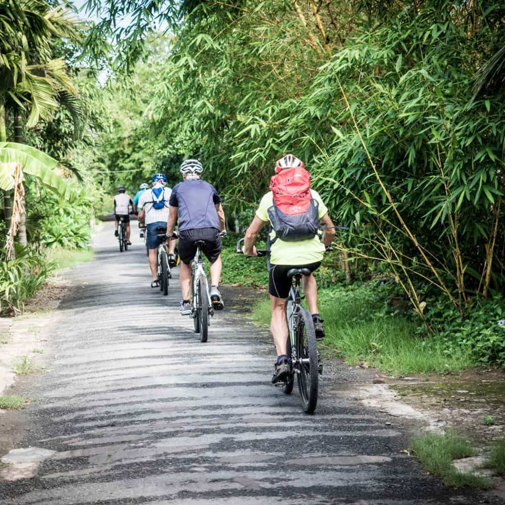 Cyclists on a small path in South Vietnam