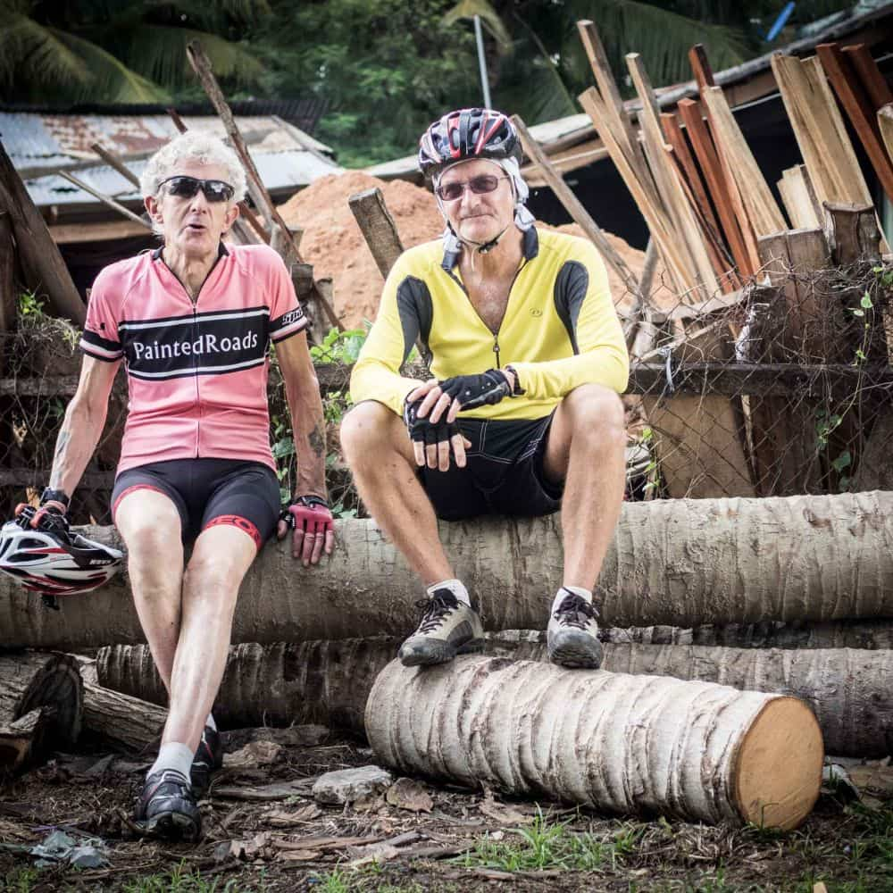 Two cyclists resting on a pole of logs in Vietnam