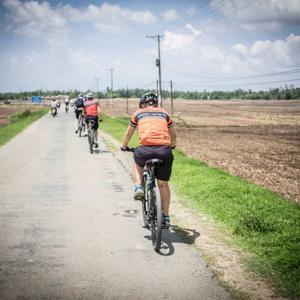 Cyclists on small empty byway in south Vietnam