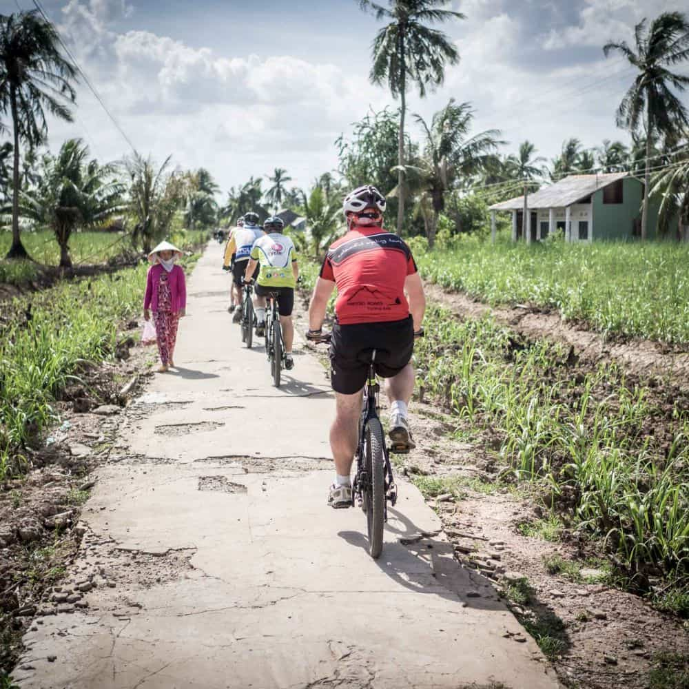 Cyclists on small empty paths in south Vietnam