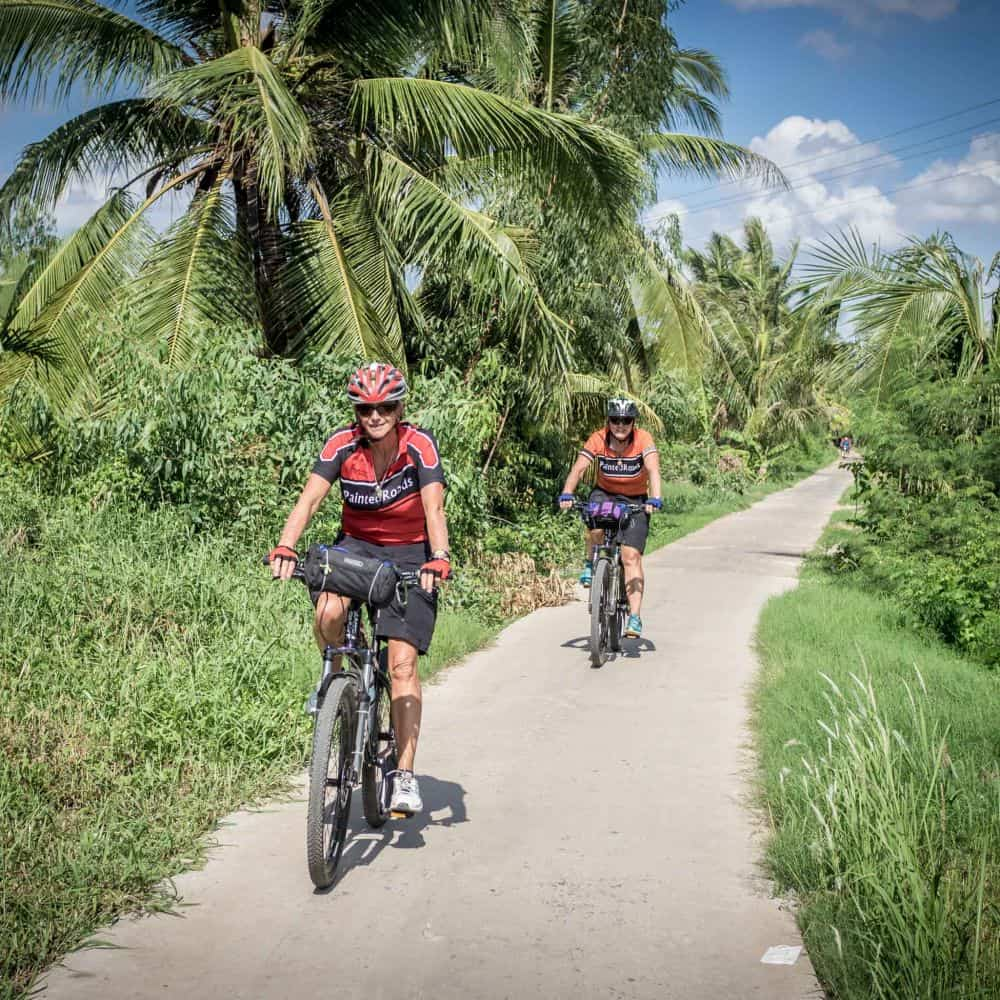 Cyclists on small empty path in south Vietnam