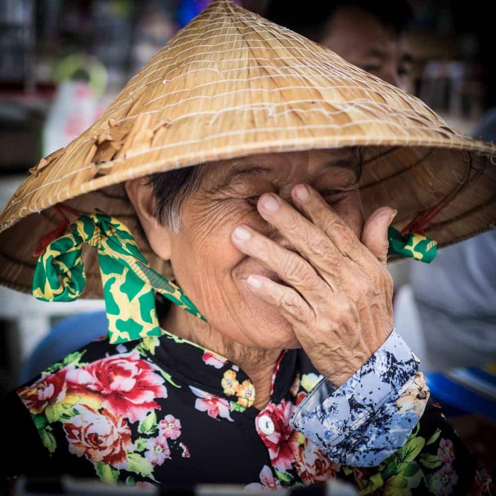 A laughing Vietnamese lady hides her face with her hand