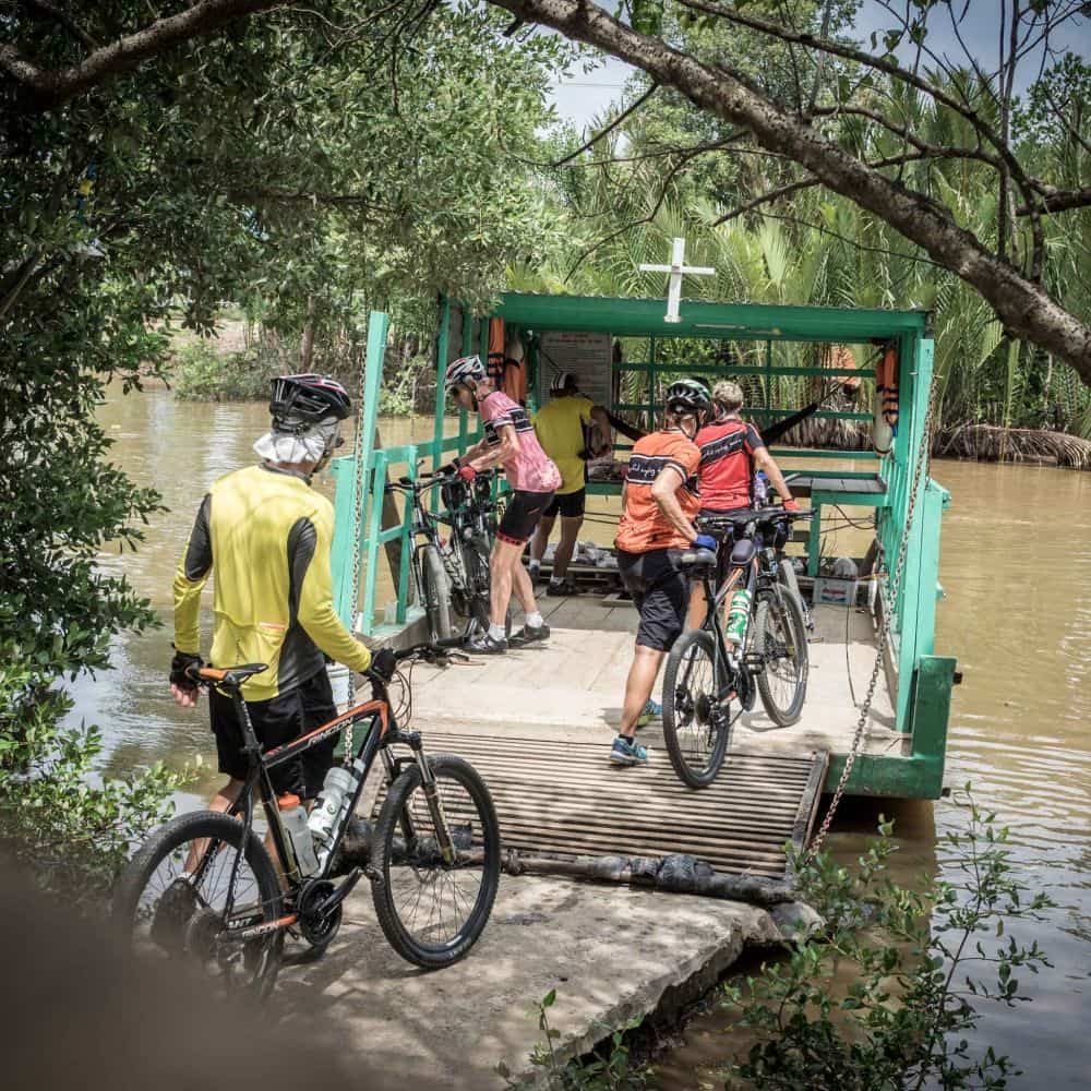 cyclists boarding a very small ferry in Vietnam's Mekong Delta