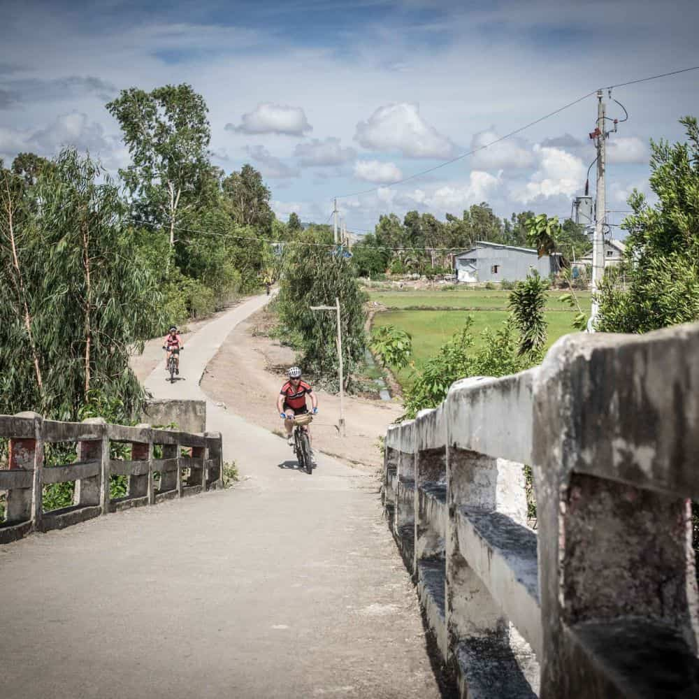 A cyclist on a quiet lane during a Mekong Delta tour