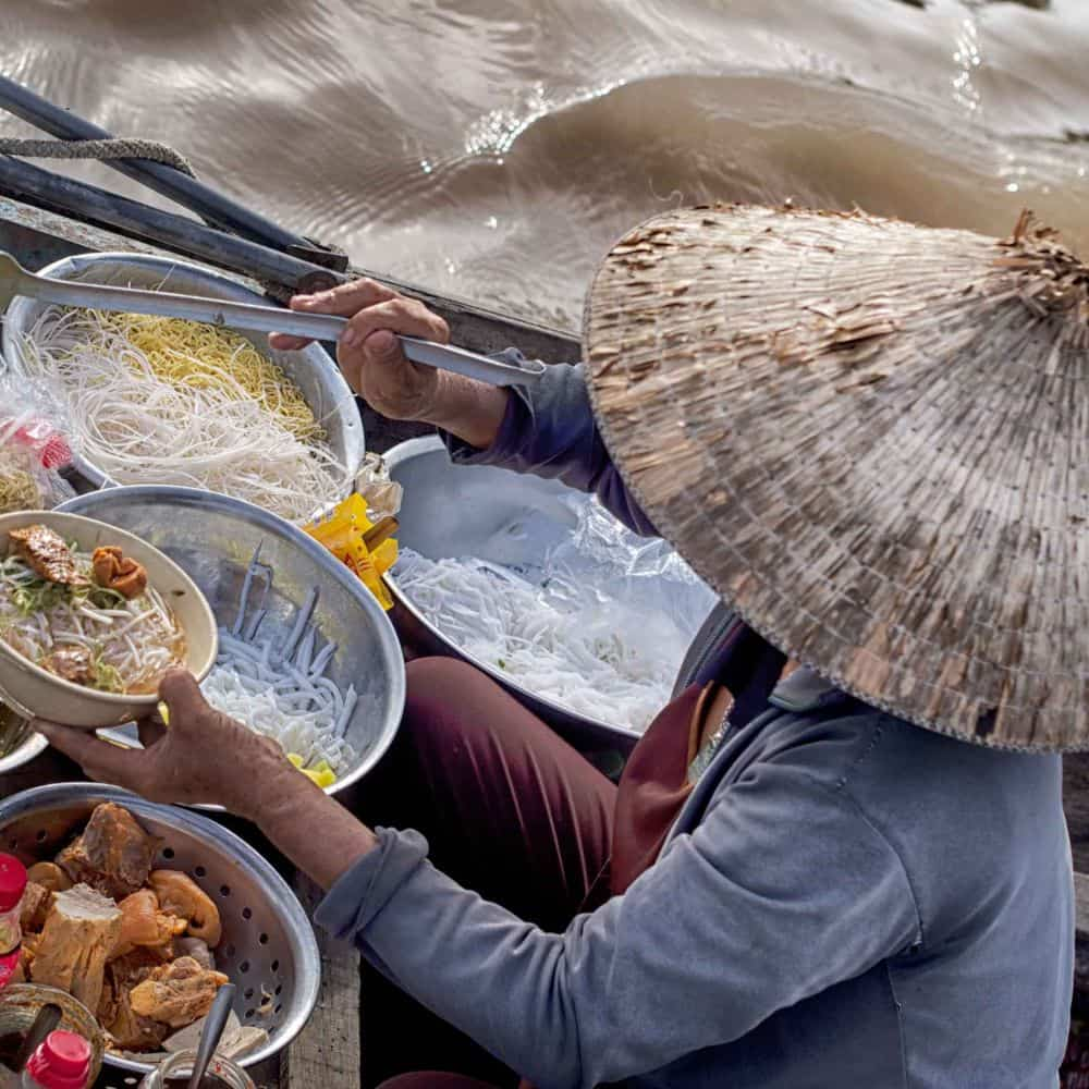 A lady prepares noodle soup aboard a boat in South Vietnam