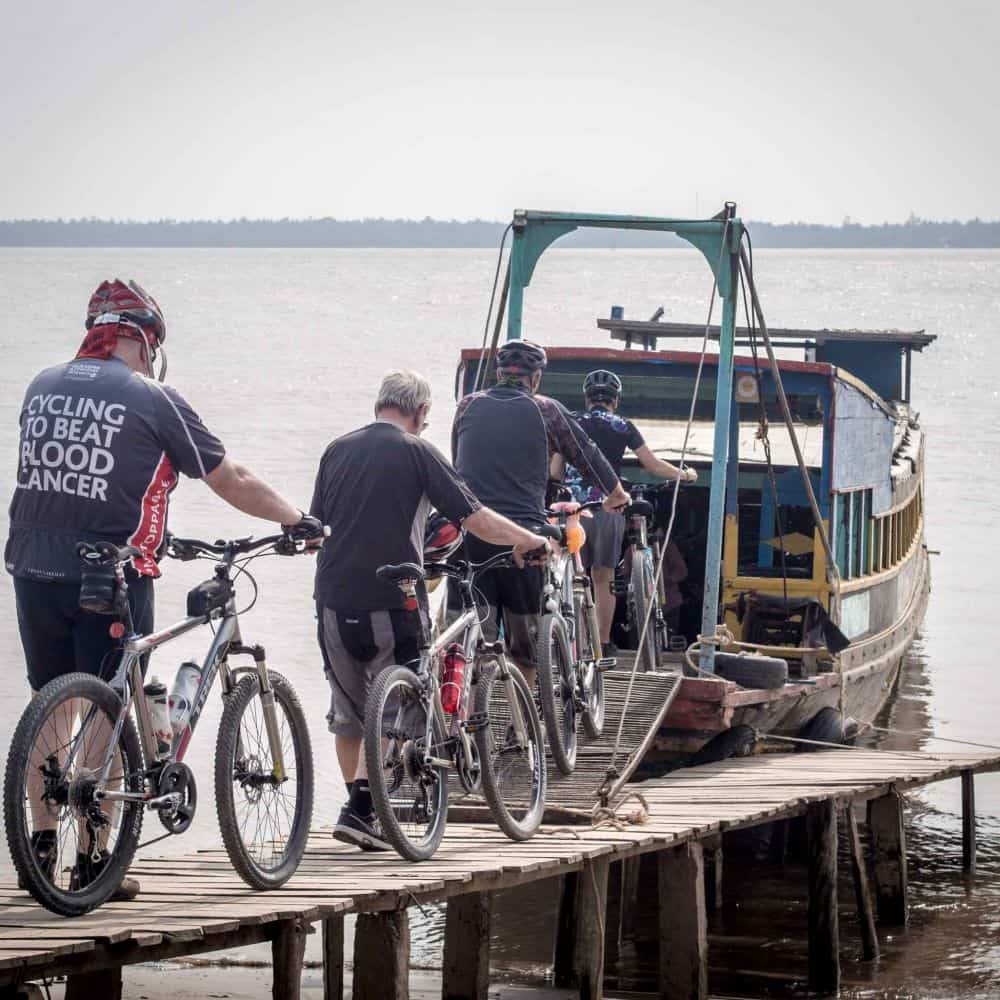 Cyclists board a boat on a Mekong Delta tour in Vietnam