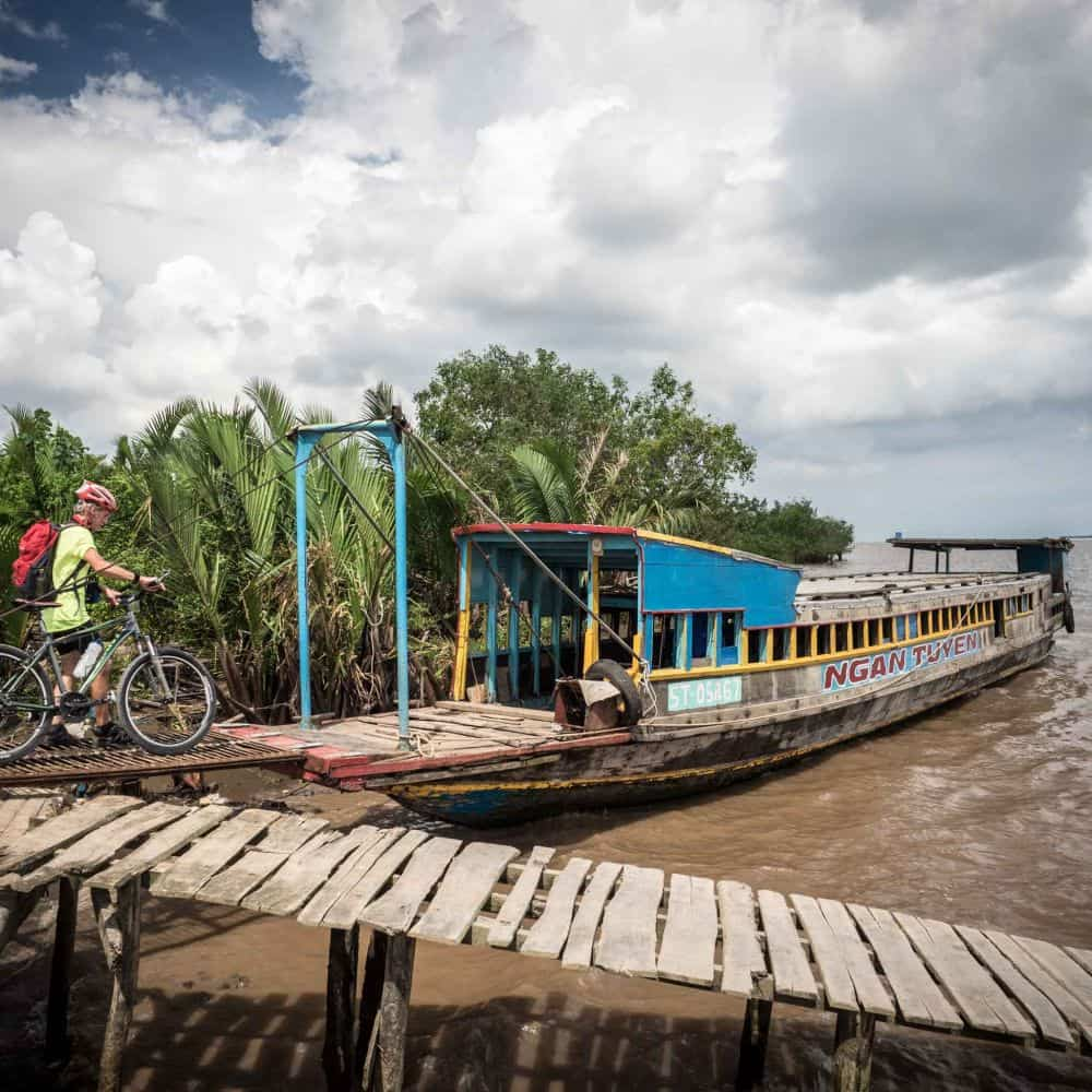 cyclists board a cross Mekong ferry in Vietnam