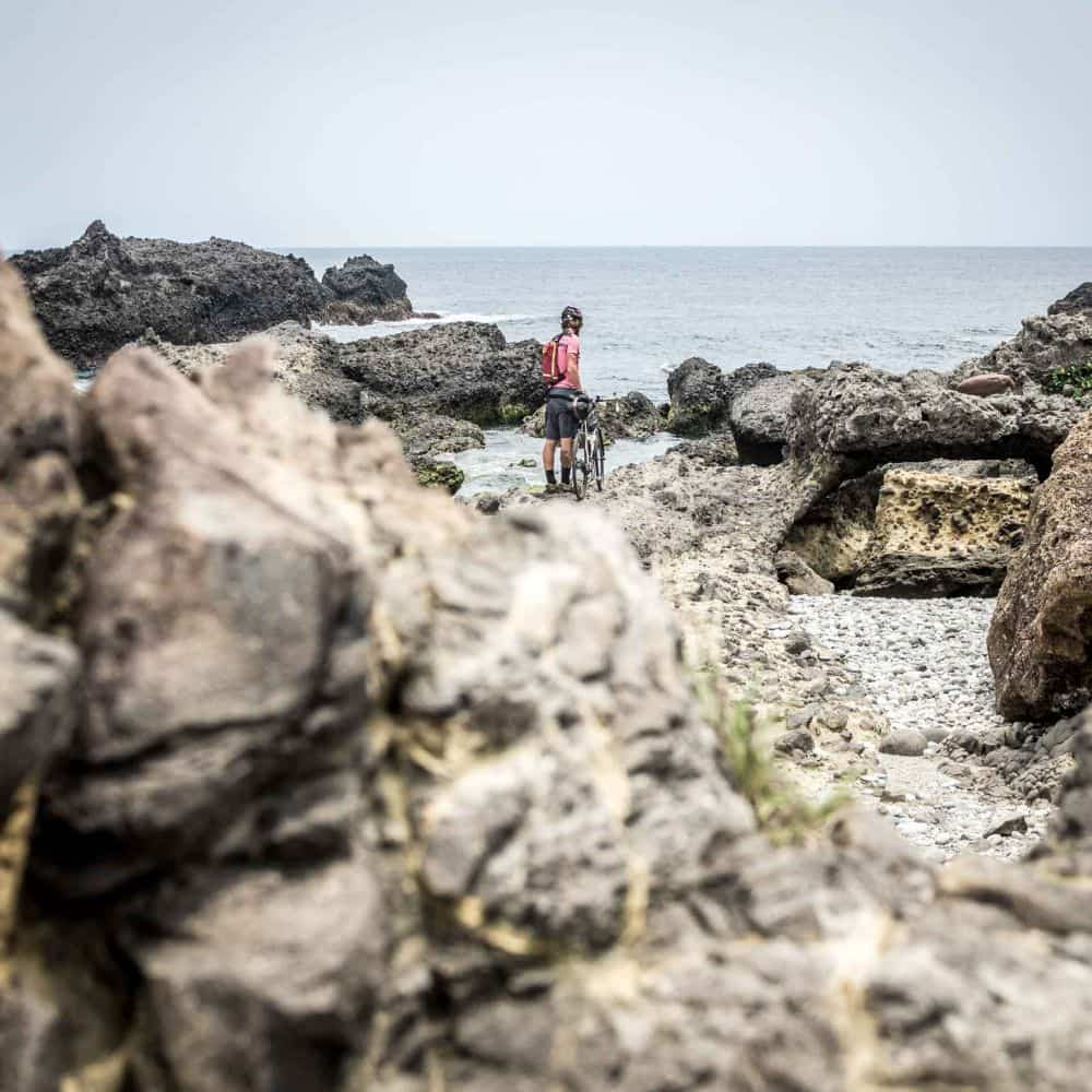 Touring cyclist on rocky beach in Taiwan