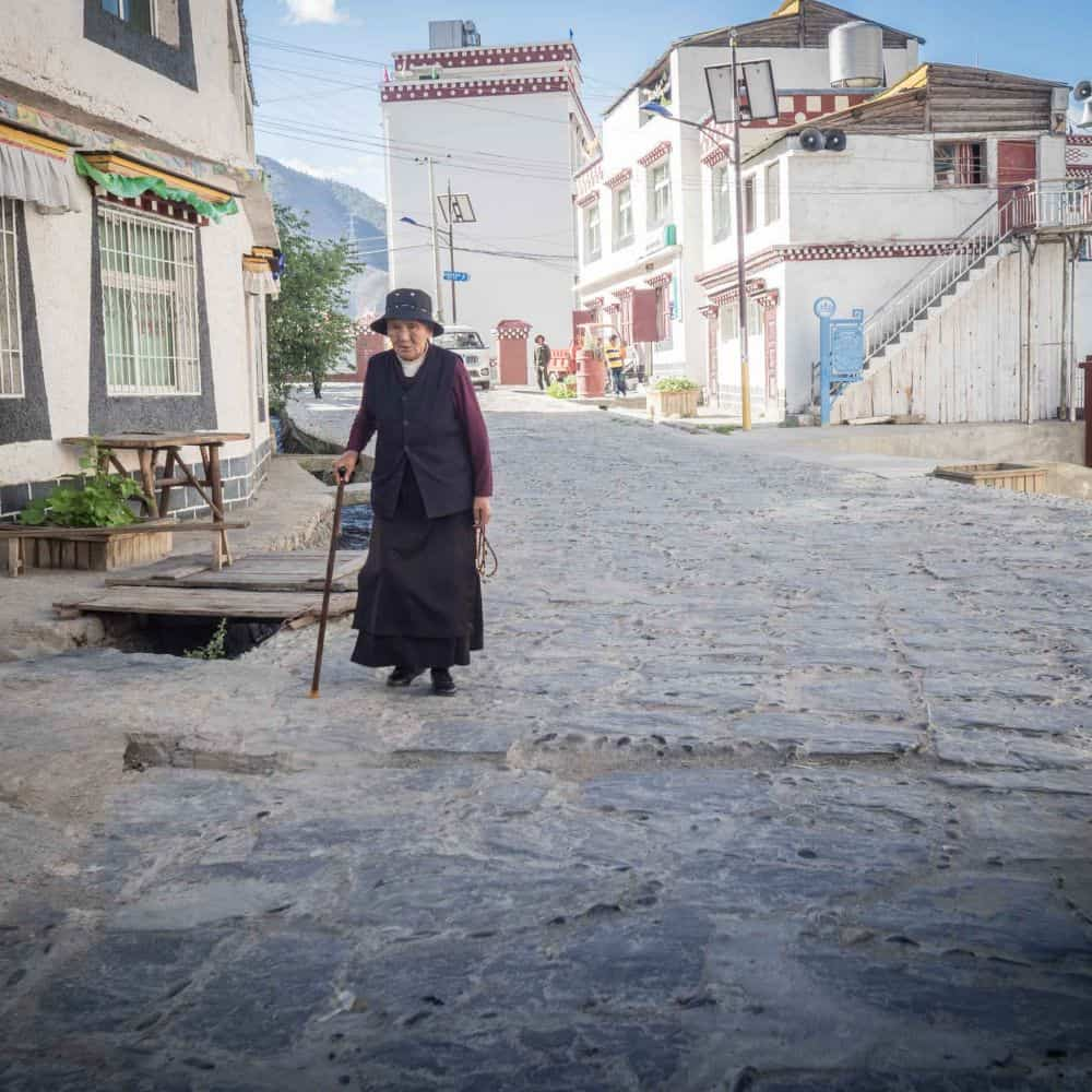 Old lady in street of flag stone and white Tibetan houses in Sichuan province China