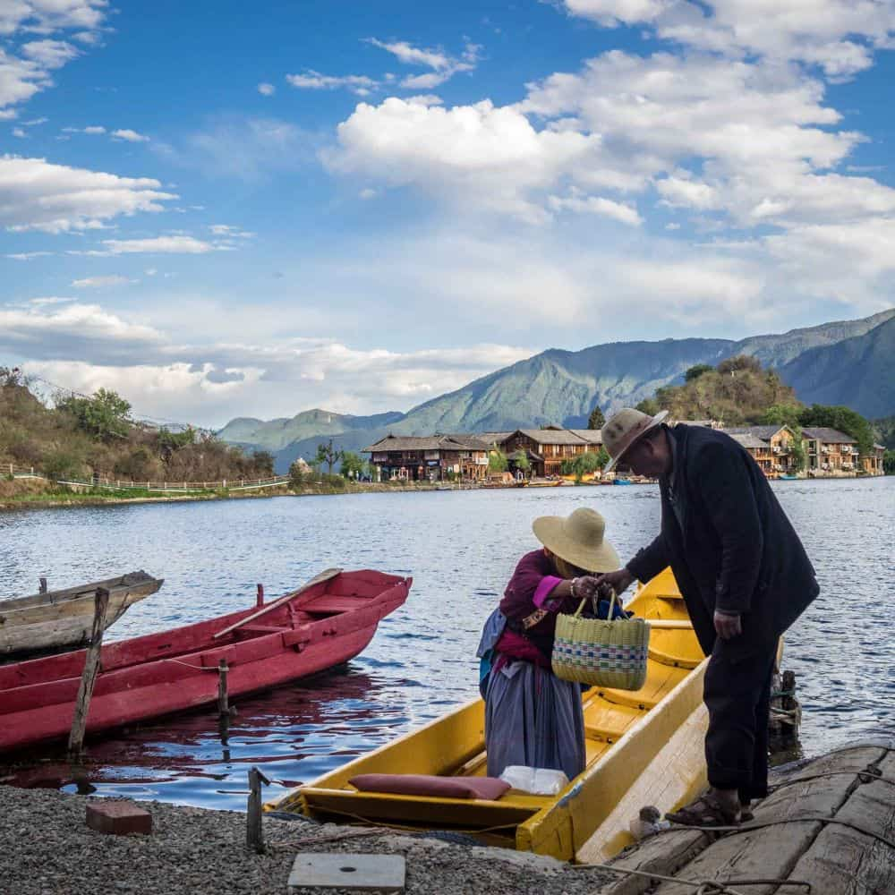 An old man helps an old lady off a boat Lugu Lake Sichuan China