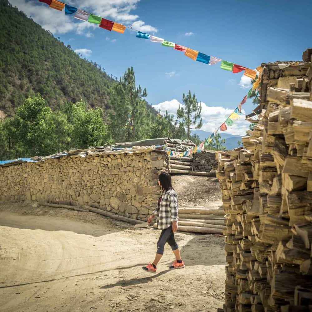 Tibetan prayer flags over gravel road with Chinese girl Sichuan China