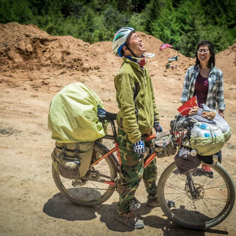 An adventure cyclist on a gravel road in Eastern Tibet Sichuan Province China
