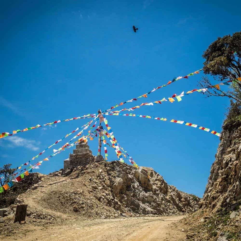 Prayer flags bird and blue sky above a gravel road on a high pass during a cycling tour in Eastern Tibet Sichuan China