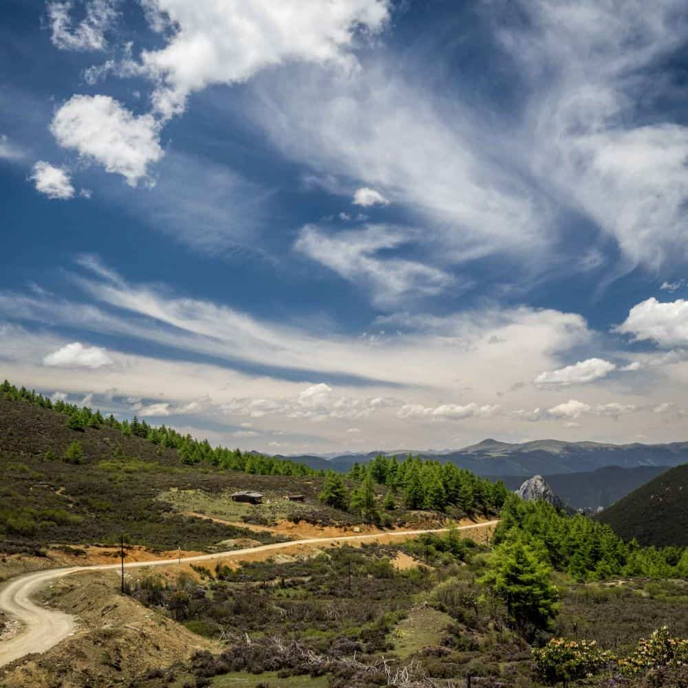 a white gravel road over a high pass on a cycling tour in Sichuan China